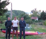 Two Bulgarian police posed with Kelsey near Grandma Mita's place. Our cabin for the night is in the background.